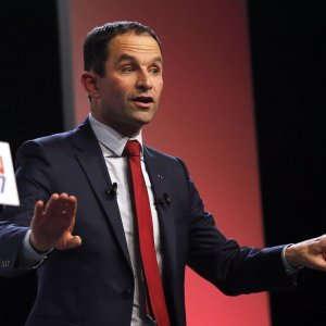"""""""Stasera la sinistra rialza la testa"""". Benoît Hamon saluta così i militanti radunati alla Mutualité nel quinto arrondissement. E' lui, 49 anni, il candidato del partito socialista all'Eliseo. Hamon trionfa nelle primarie con il 58% dei voti rispetto al 41% dell'avversario Manuel Valls. L'ex premier è stato battuto con un largo scarto, pagando l'eredità del suo governo e l'impopolarità di François Hollande. Valls ha augurato """"buona fortuna"""" al suo rivale che, con poco fair play, l'ha interrotto mentre stava salutando i suoi sostenitori.    Il candidato prescelto, su cui nessuno o quasi avrebbe scommesso fino a qualche settimana fa, è il simbolo di una svolta verso la base più radicale della sinistra. Il suo programma è stato definito dall'avversario """"utopico"""": orario di lavoro a 32 ore settimanali, reddito universale per tutti i cittadini pagato dallo Stato, nuova tassa sui robot per le imprese. Il """"Sanders alla francese"""" rappresenta un ritorno al """"socialismo rivoluzionario"""" di altri tempi dopo cinque anni di esercizio di governo che hanno profondamente spaccato la gauche. """"Dobbiamo immaginare risposte nuove, riflettere sul mondo per com'è e non per com'era"""" ha spiegato Hamon nel discorso di vittoria, con la mano sul cuore, il gesto diventato il suo marchio di fabbrica e lo slogan della sua campagna (""""Far battere il cuore della Francia"""").  """"Vogliamo vincere"""" ha promesso ancora Hamon, nonostante i sondaggi siano per lui poco favorevoli. Il candidato del Ps deve affrontare una forte concorrenza sull'estrema sinistra: sia il gauchiste Jean-Luc Mélenchon che il verde Yannick Jadot. E' a questi concorrenti diretti che ha lanciato un primo appello per aprire un """"dialogo"""", con la speranza che almeno uno dei due faccia desistenza. I sondaggi prevedono infatti finora l'eliminazione sicura di Hamon al primo turno delle presidenziali del 23 aprile.  Il nuovo candidato non ha invece detto una parola su Emmanuel Macron, altro avversario che mette a repentaglio le chances del soci"""